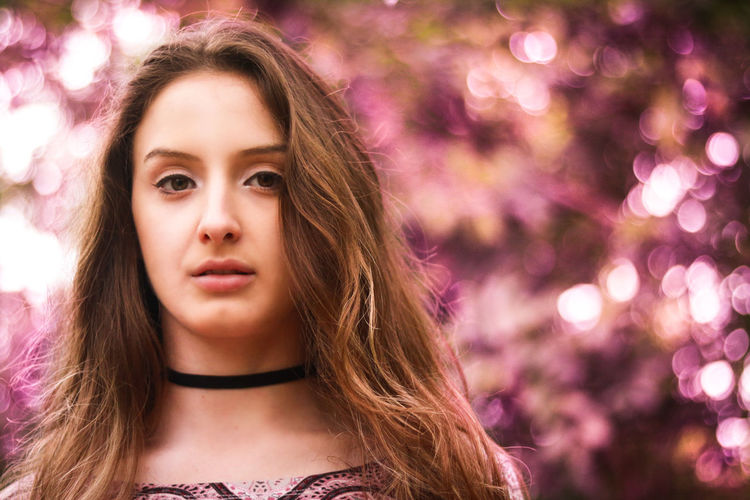 Beautiful Woman Beauty Childhood Close-up Flower Focus On Foreground Front View Headshot Illuminated Lifestyles Long Hair Looking At Camera Nature Night One Person Outdoors People Portrait Purple Real People Tree Young Adult Young Women