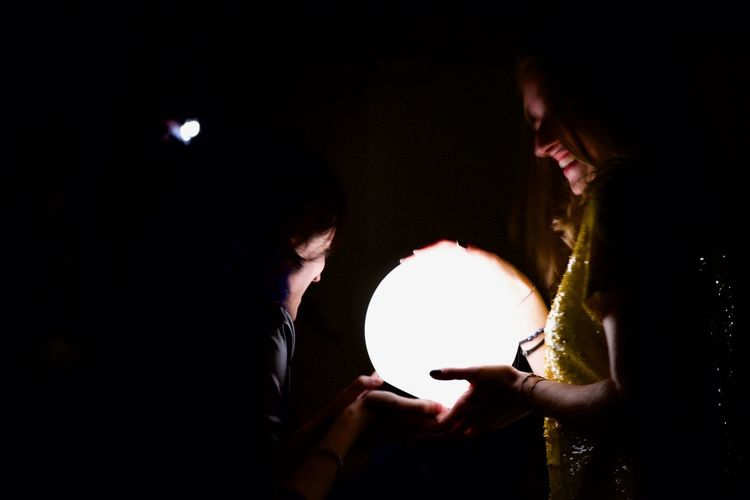 People holding lit candle in the dark