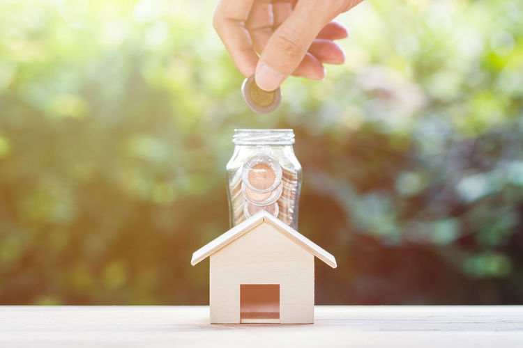 Saving money, home loan, mortgage, a property investment for future concept : A man hand putting coins over small residence house and glass jar with green nature background. A sustainable investment. Business Home Body Part Business Close-up Estate Finance Finance And Economy Finger Hand Holding House Human Body Part Human Hand Investment Jar Mortgage Nature Property Real People Save Savings Table Tax Wood - Material