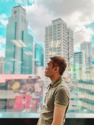 Side view of man looking at city buildings