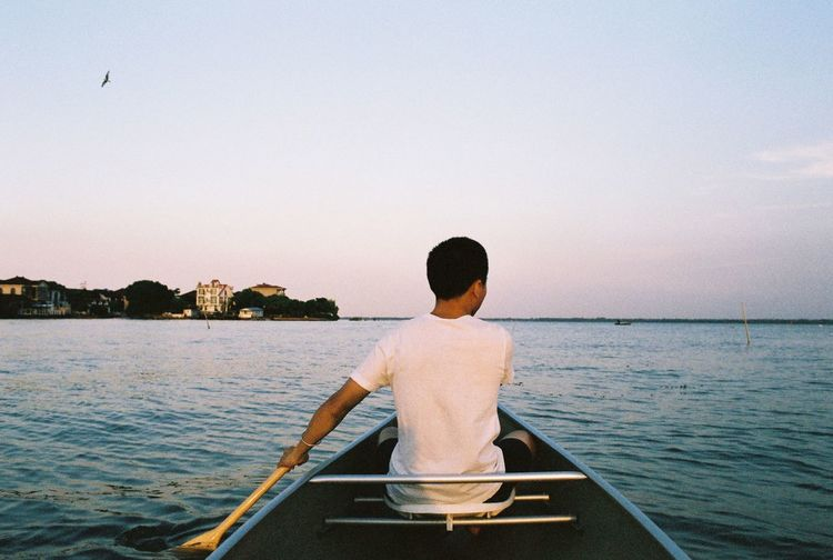 Rear View Of Man Rowing Boat In Sea During Sunset