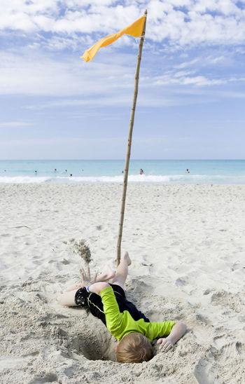 Playful Boy At Beach Against Sky