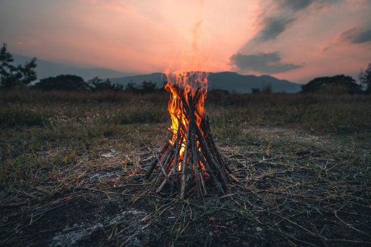 Bonfire on field against sky at sunset