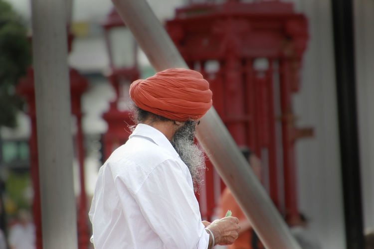 Side view of man wearing turban while standing outdoors