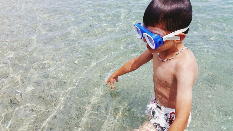 Shirtless boy in sea