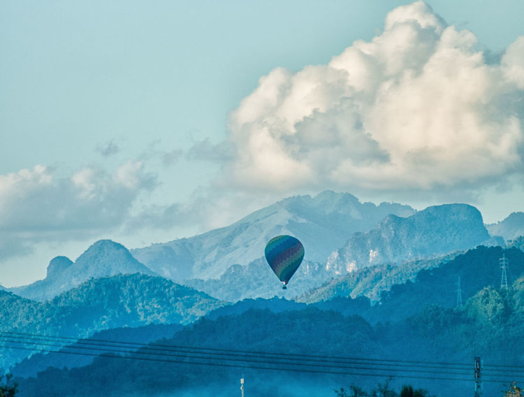 Hot air balloon flying over mountain range on cloudy sky. Adventure Beauty In Nature Cable Cloud - Sky Cloudy Cold Temperature Day Electric Flying Hot Air Balloon Low Angle View Mid-air Mountain Mountain Range Nature Outdoors Pattern Scenics Sky Tranquility Weather Winter