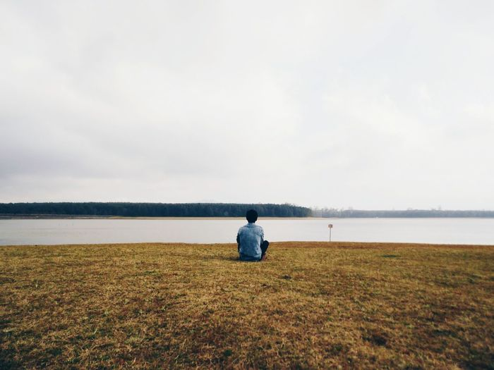 Rear view of man sitting at riverbank against sky