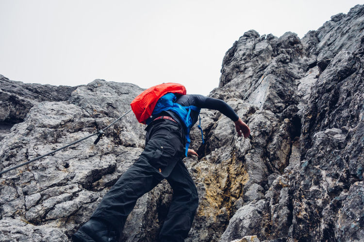 Rear view of man on cliff against mountain