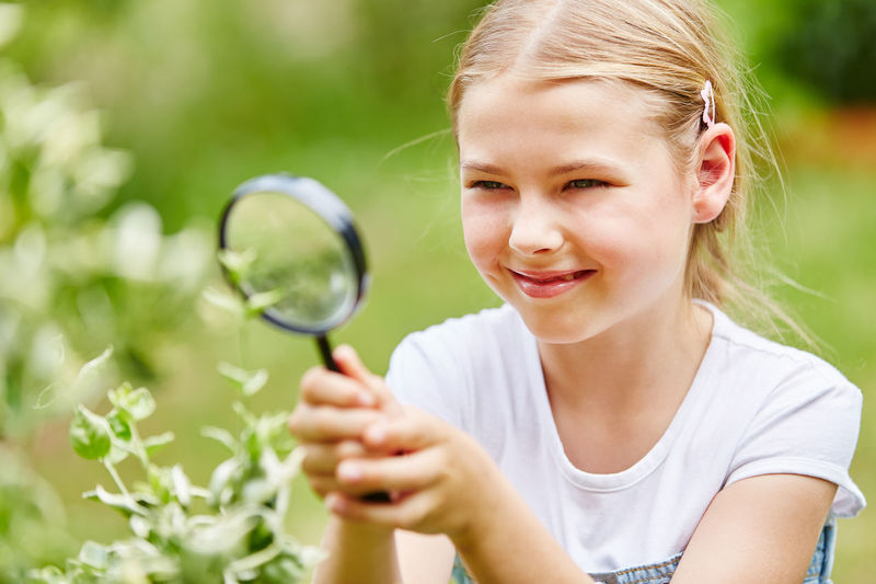 Smiling girl looking at plants through magnifying glass