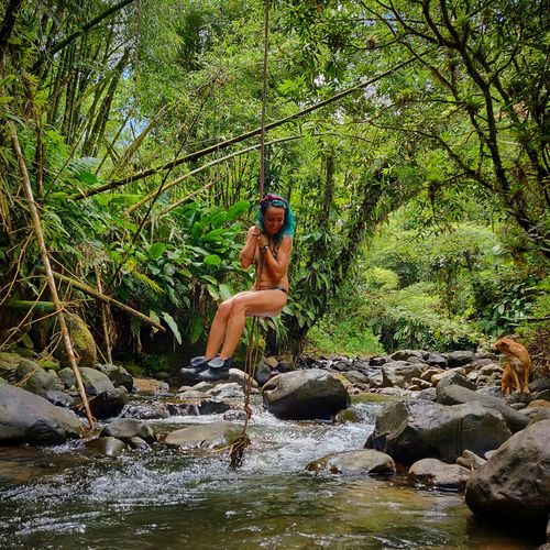 Young woman in river amidst trees in forest