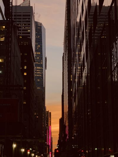 Low angle view of buildings in city at sunset