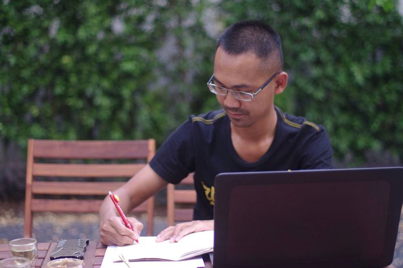 Man writing in paper while sitting outdoors