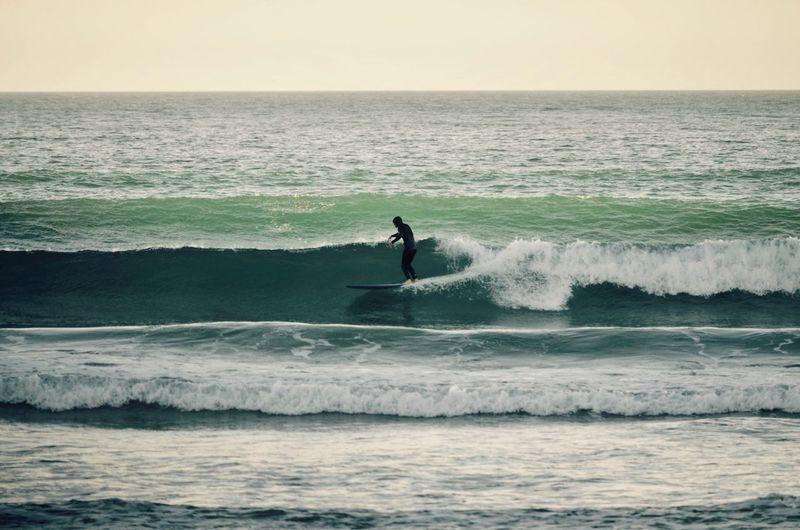 Man surfing in sea against sky