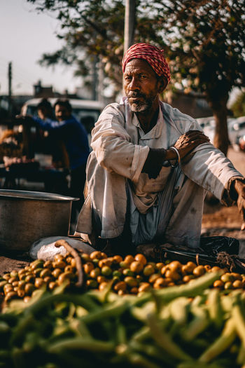 Midsection of man with vegetables at market stall