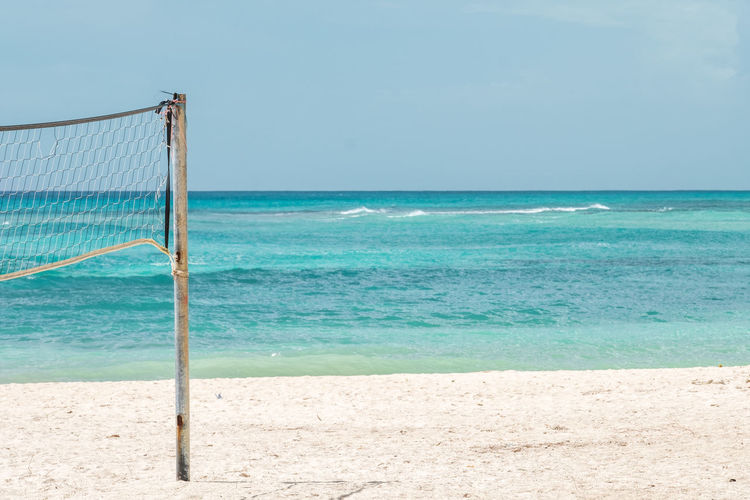 Sea Beach Land Water Sky Horizon Over Water Sport Net - Sports Equipment Nature Beauty In Nature Sand Scenics - Nature Blue Tranquility Day Outdoors Tranquil Scene No People Turquoise Colored Volleyball Vacations Beach Holiday Copy Space Pole Turquoise Colored