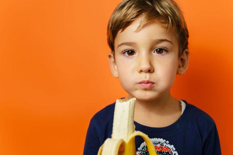 Close-up portrait of cute boy holding orange