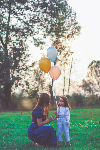 Girl with balloons on field by trees