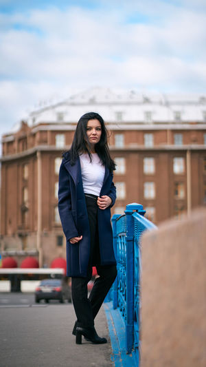 Full length of beautiful young woman standing in city