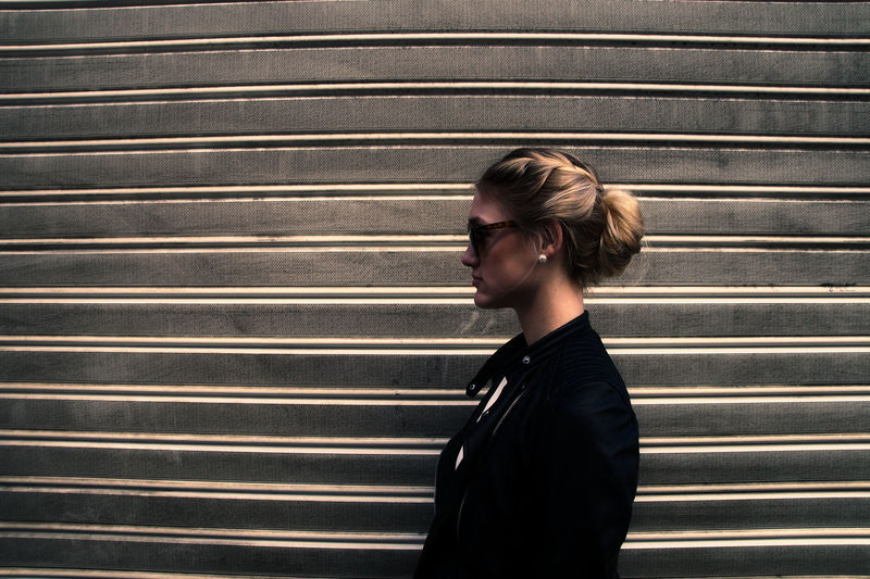 Side view of woman wearing sunglasses against wall