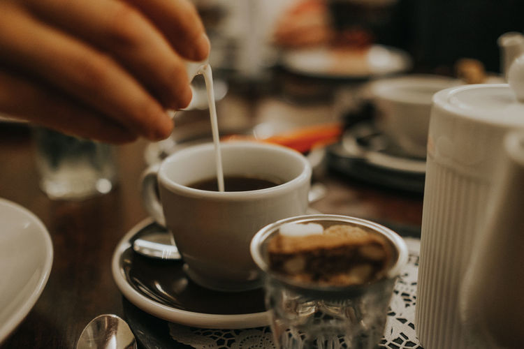 Cropped Image Of Hand Pouring Milk In Coffee Cup At Table