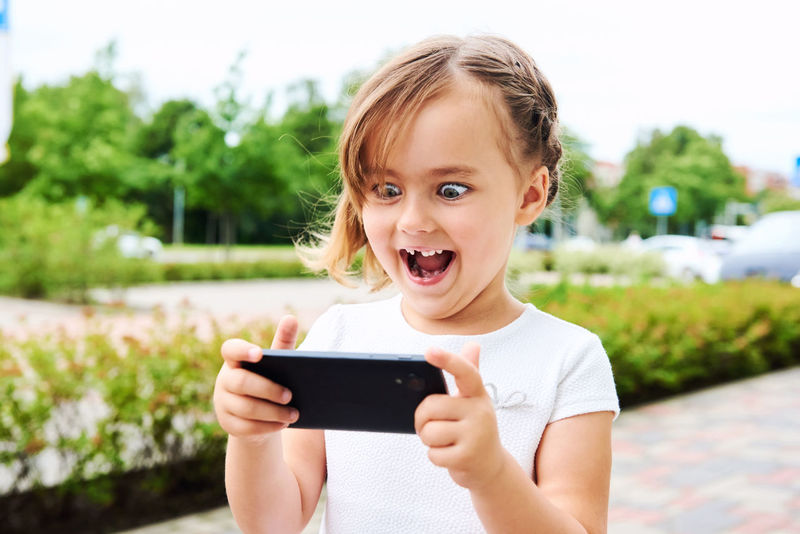 Adorable expressive little girl with a smartphone outdoors 5 Years Old Alone Beautiful Caucasian Cell Cellphone Child Daughter Device Emotions Expression Fun Gaming Internet Leisure Little Girl Mobile Phone Outdoors Phone Play Player Small Girl Smartphone Summer Technology