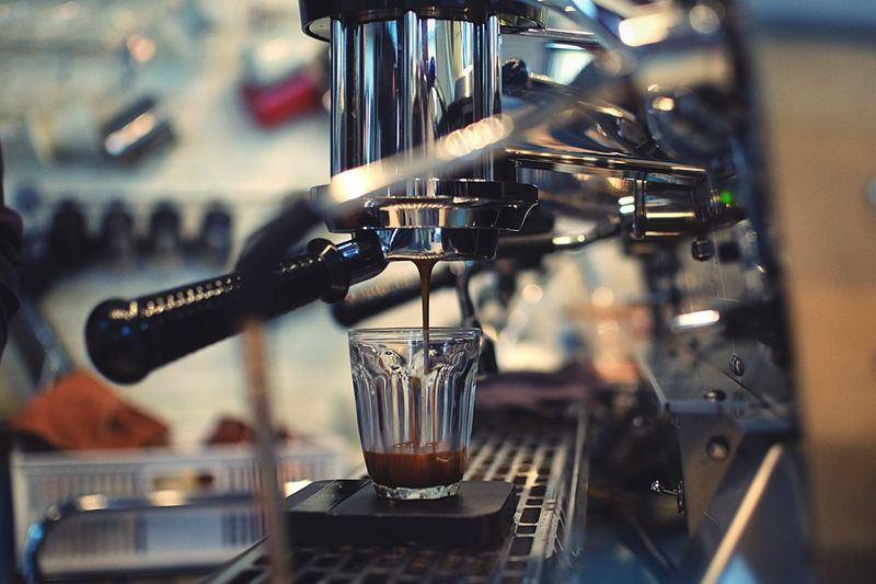 Close-up of espresso maker pouring coffee in cup at cafe