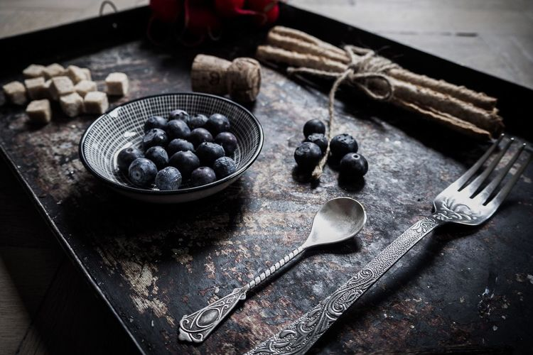 High Angle View Of Blueberries With Spoon And Fork On Tray
