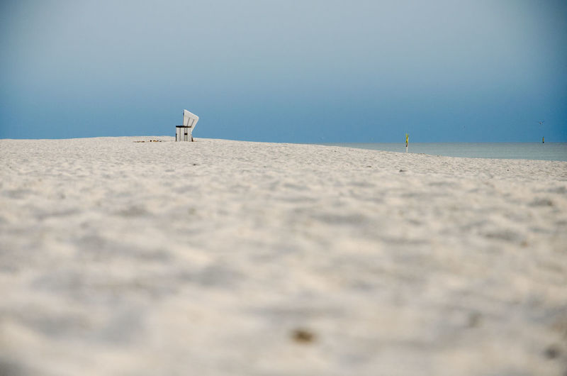 Mid Distance View Of Hooded Beach Chair At Beach Against Blue Sky