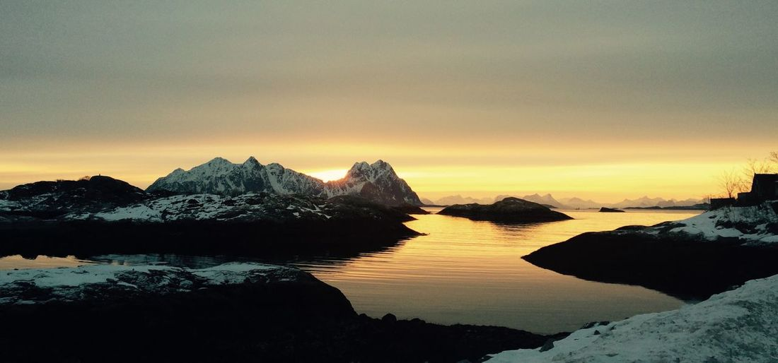 Scenic view of sea by snowcapped mountains against sky during sunset