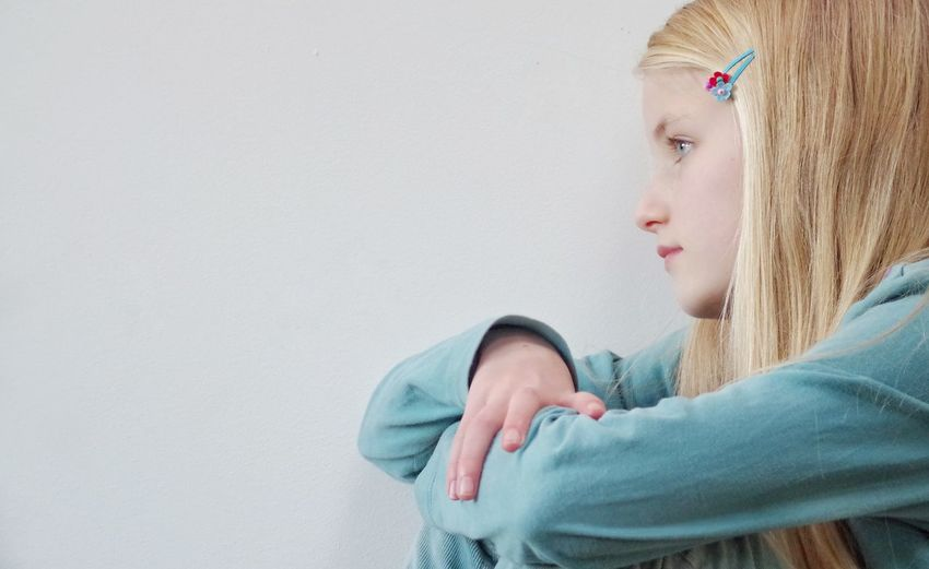 Side view of sad girl against white background
