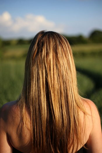 Rear view of blond woman standing on field