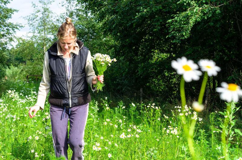 Full length of woman standing on flowering plant