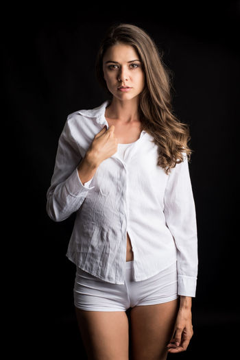 Portrait Young Adult Looking At Camera Black Background One Person Studio Shot Women Beauty Hair Beautiful Woman Hairstyle Adult Three Quarter Length Indoors  Long Hair Young Women Standing Beautiful People Fashion Shorts Contemplation