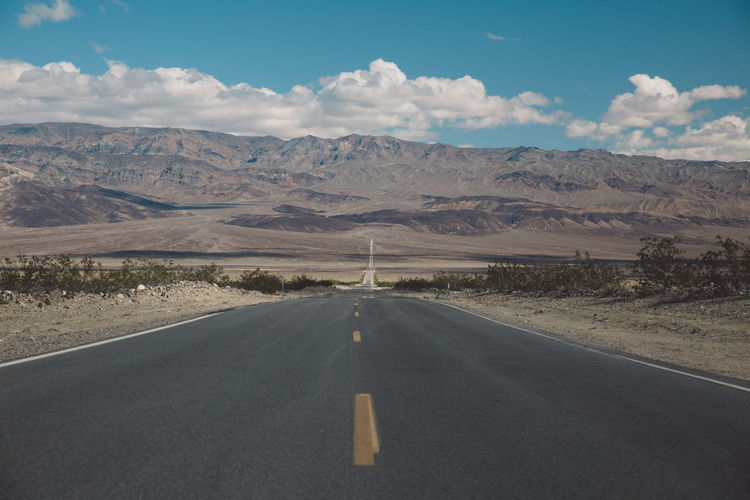 Arid Climate Arid Landscape Asphalt Blue Sky Cloud - Sky Day Death Valley Death Valley National Park Desert Landscape Mountain Mountain Range Mountains Nature Nature No People Outdoors Road Road Marking Roadtrip Scenics Sky The Way Forward Tranquil Scene Transportation