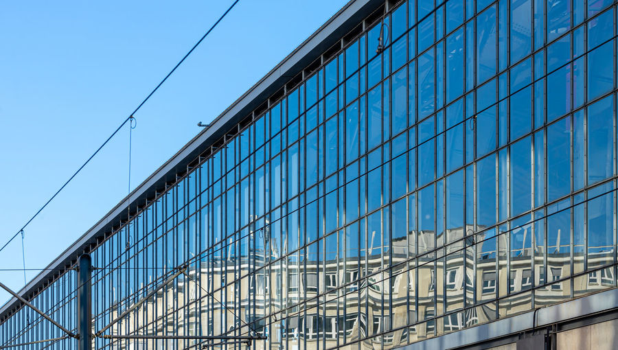 Low angle view of modern glass building against blue sky