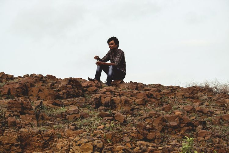 Young man sitting on rock against sky