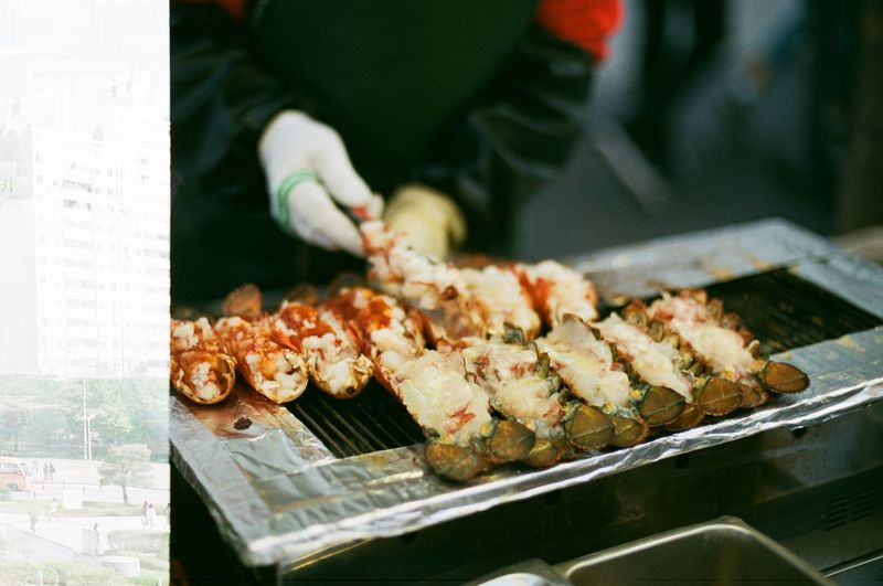 Close-up of man holding meat on barbeque grill