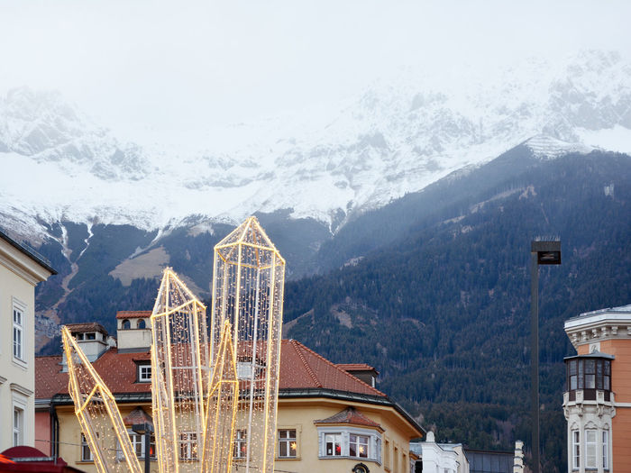 Buildings in city against snowcapped mountains during winter