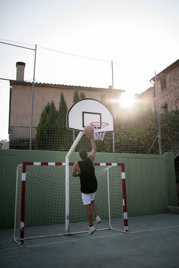 Rear view of mid adult man playing basketball against clear sky at sunset