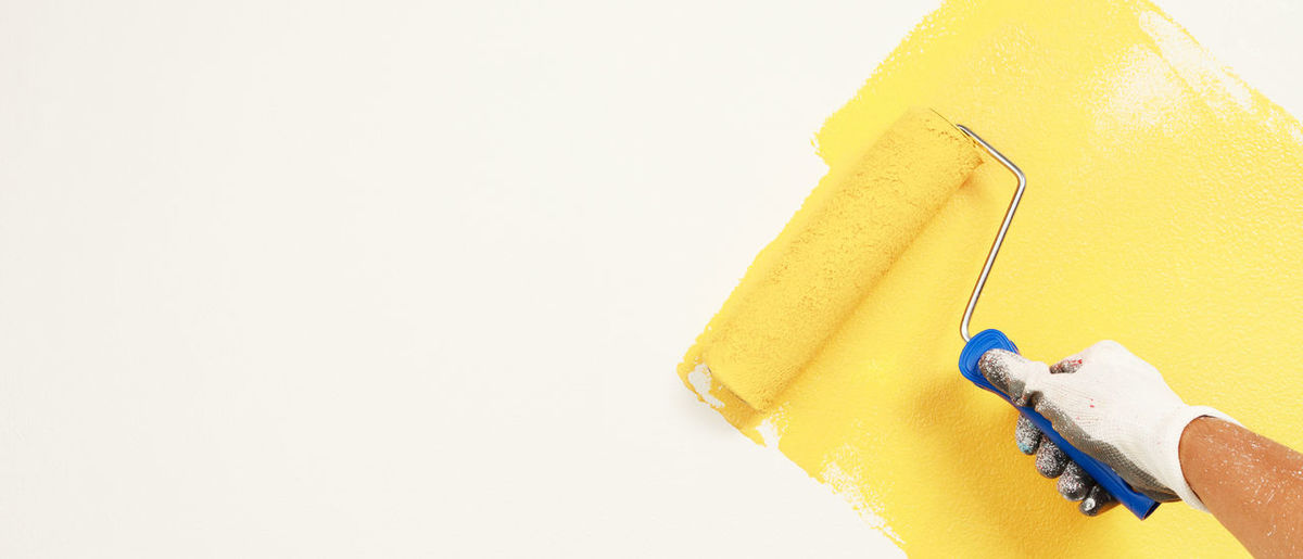 Close-up of hand holding yellow paper over white background