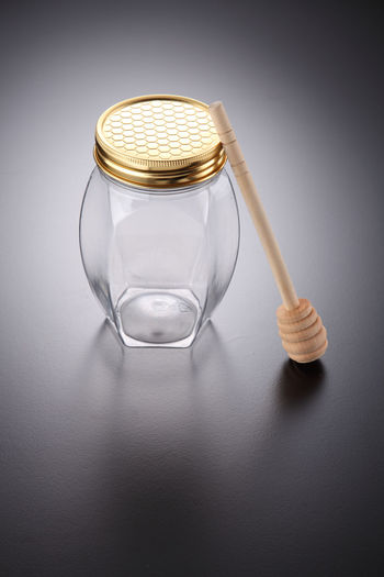 Glass jar and honey dipper on gray background