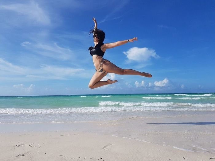 Low angle view of women jumping at beach against sky