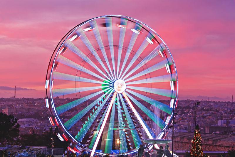 Ferris wheel in city against cloudy sky