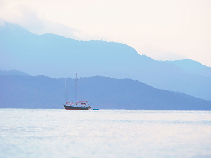Lonely boat on clam sea background. pastel colors.