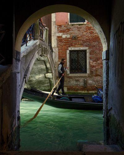 Man rowing boat in canal against bridge