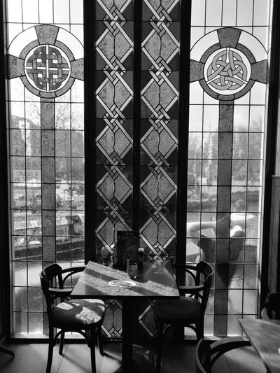 Chairs And Table Against Stained Glass At Restaurant