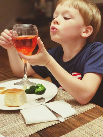 Young boy enjoying flavored ginger ale in a wine glass Glassware Satisfying Quenching My Thirst  Thirsty  Christmas Dinner Drinking Soda  Hydration Hydrating Fancy Glass Drinking Juice Holding Glass Holding Young Boy Young Child Drinking Content Enjoyment Food And Drink Drink Wineglass Real People Drinking Glass Table One Person Refreshment People Close-up