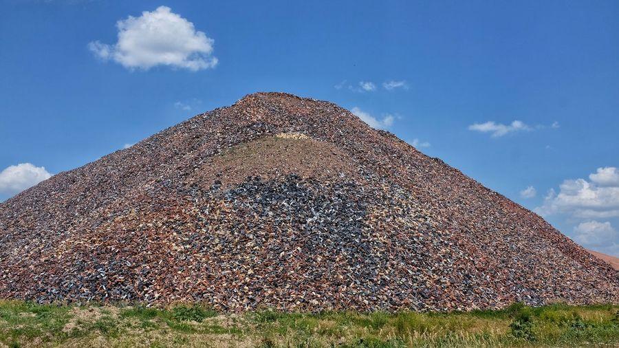 Pile of discarded bricks against sky