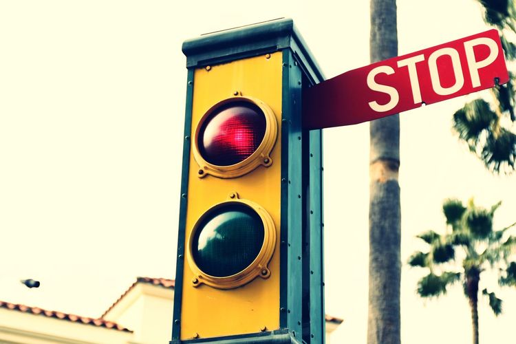 Illuminated stoplight road signal against sky