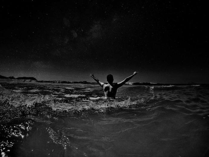 Rear View Of Shirtless Man Swimming In Sea At Night